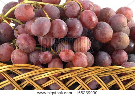 Red vine grape branch in brown wicker basket isolated on white