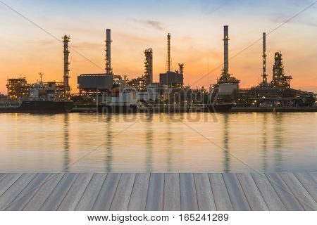 Opening wooden floor Oil refinery river front during sunrise sky background
