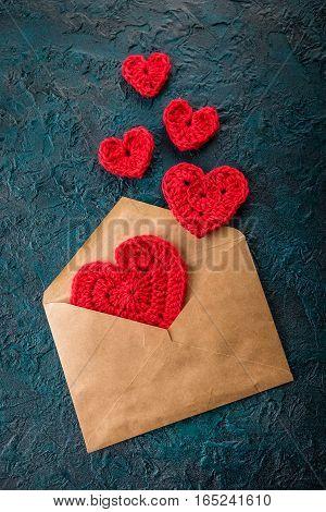 Crochet valentine hearts and envelope on dark background.