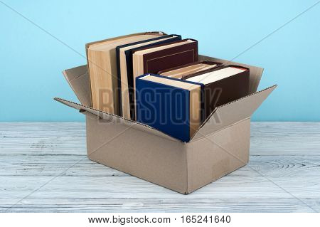 Book stacking in paper box. Open book, hardback books on wooden table and blue background. Back to school. Copy space for text