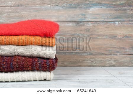 A stack of woolen sweater plaid. Warm clothing. Home atmosphere winter clothing. Red white and brown sweater. Warm and cozy. Knitted clothes. wooden background