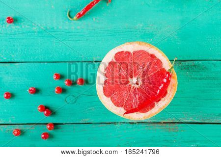 Half of grapefruit on a wooden turquoise background. Copyspace. Colorful festive still life.