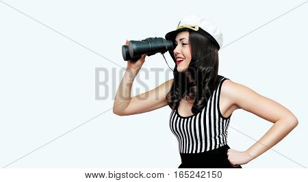 Travel cruise people concept - pretty smiling woman brunette sailor looking through binoculars pin-up style over empty copy space white background
