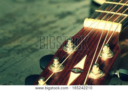 The head of the guitar with strings on a wooden background.