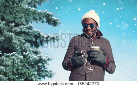 Winter Young Smiling African Man Enjoying Listening Music On Smartphone With Paper Cup Of Coffee Ove