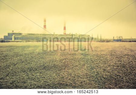 Gas power plant. Pipes with smoke. Lake with fog foreground. Energy industry concept. Toned.