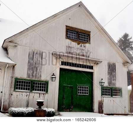 Old New England style white barn with a green barn door on a gray snowy January day