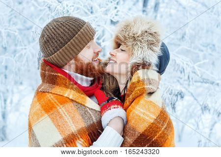 Happy romantic smiling lovers hugging on snowy winter outdoor. Winter love story. People, season, leisure and love concept. Young family couple covered with plaid blanket in winter forest