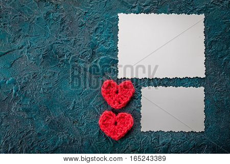 Crochet valentine hearts and greeting card on dark background.