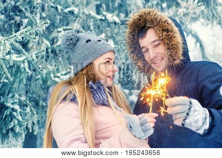 Couple holding sparklers. Young couple with sparklers in winter forest. Smiling family with bengal lights. Happy smiling couple with holiday sparklers celebrating Christmas outdoors