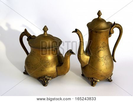 Antique brass coffeepot and teapot with a pattern ion white background with shadows
