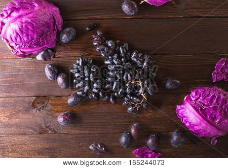 Blue grapes and plums on a wooden background