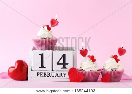 Tasty cupcakes with cube calendar on pink background
