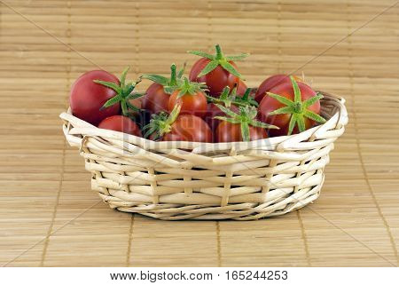 Still life with red tomatoes in wicker basket on straw mat closeup. Horizontal view