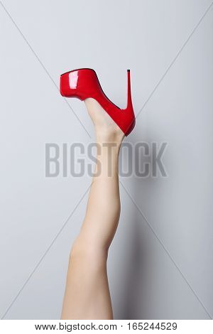 Female Leg With Red High Heels On A Grey Background
