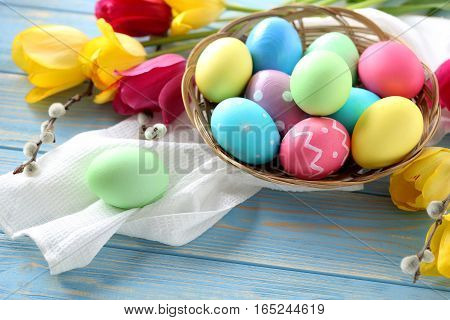 Easter Eggs In Basket On A Blue Wooden Table
