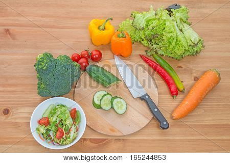 Chopped salad and whole fresh vegetables on wooden table. Top view