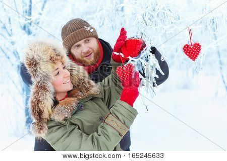 Love story in the winter forest with red hearts. Young romantic couple outdoor. Happy couple in winter clothes holding red heart. Winter love story. Valentine's Day and love concept