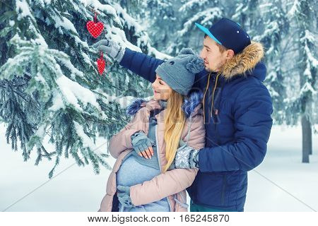 Young pregnant couple in winter forest. Happy man and expectant mother waiting for baby in winter. Love, family, pregnancy concept. Future parents walking outdoors