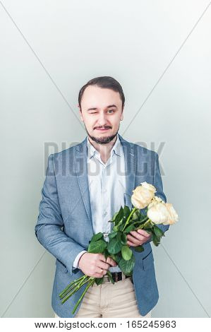 Handsome man with beard standing against a grey background with a bouquet of white roses. Business man gives roses to the occasion.