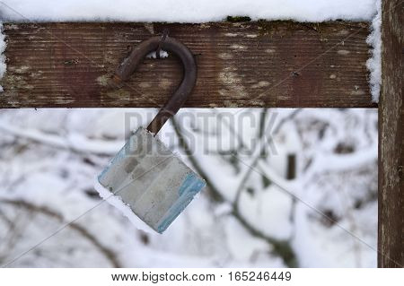 Abandoned unlocekd padlock hanging on the wooden fence, cropeed outdoor shot, concept of security