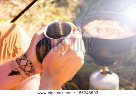 Close-up shooting of guy holding metal cup near the fireplace