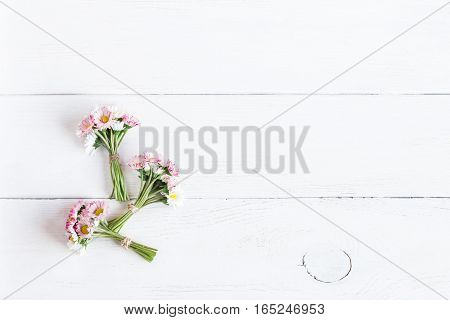 bouquet of daisy flowers on wooden white background top view flat lay