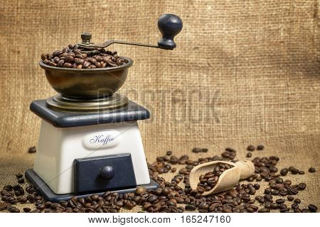 coffee grinder, coffee beans and wooden scoop on jute
