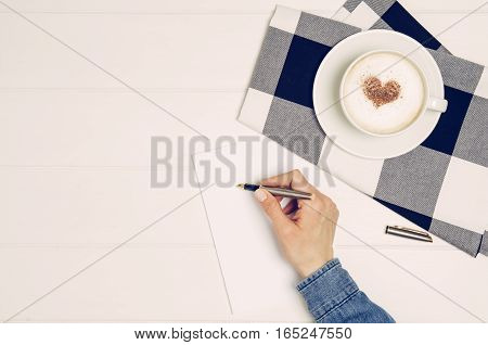 Female hand writing love letter on white wooden table. Photograph taken from above, top view with copy space