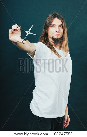Hairdresser and barber. Long haired handsome man hairstylist with scissors. Young male showing trimmers.