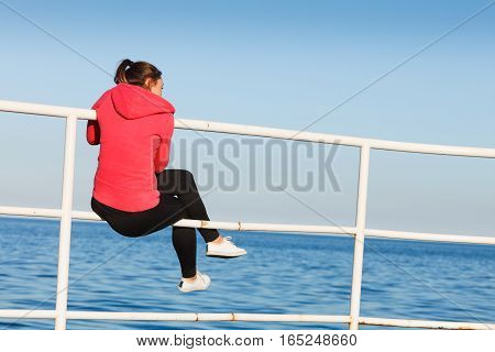 Woman Sitting On Pier Looking At Horizon Outdoors