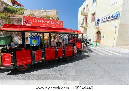 Rethymno Island Crete Greece - June 23 2016: A small red train for tourists drives in the street of Rethymno for sightseeing