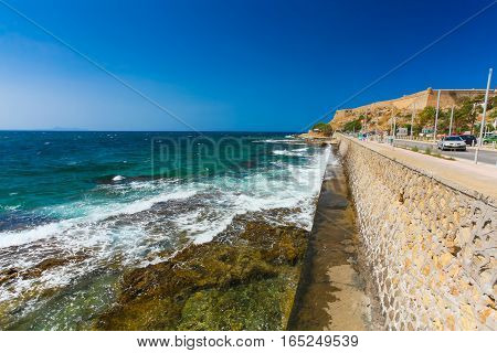 Rethymnon Island Crete Greece - July 1 2016: People are walking on Leoforos Emmanouil Kefalogianni embankment and watching on the sea with clear emerald water and sharp underwater stones.