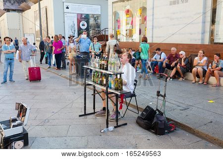 MILAN ITALY - September 06 2016: Musician is playing music on the glass bottles and singing songs in the central Milan.