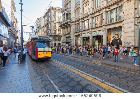 MILAN ITALY - September 06 2016: People are waiting tram on the station for public transport on the Torino street (Via Torino) in the city center in Milan.