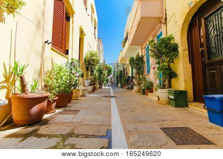 Rethymnon Island Crete Greece - June 23 2016: The narrow street of Rethymnon (part of Old Town) where there are a lot of pots with flowers