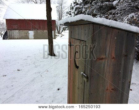 First snowfall and a 100 year old barn and small decorative outhouse in rural Illinois.