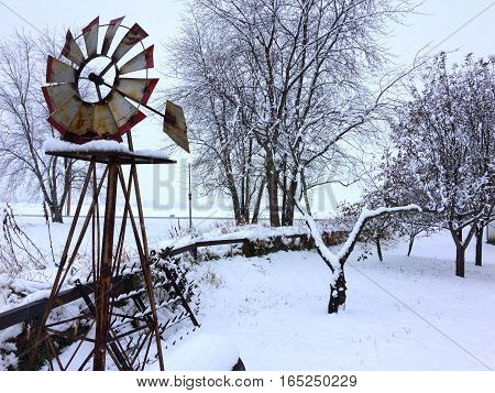 First snowfall and a small decorative garden windmill in rural Illinois.