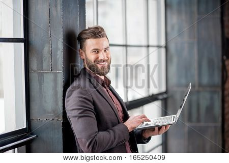 Handsome bearded businessman dressed in the suit standing with laptop near the big window in the loft interior studio