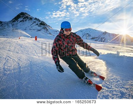 Skier on piste in high mountains with beautiful sky on sunny day. Active downhill ride.