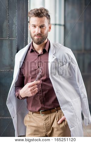 Portrait of handsome confident dentist with medical gown and dental tools standing near the window in the modern dark interior clinic or office