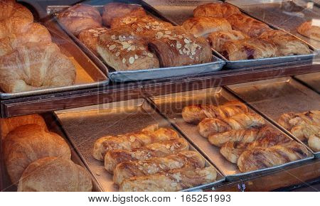 Sweet pastries, croissant breads and beignets in a bakery window