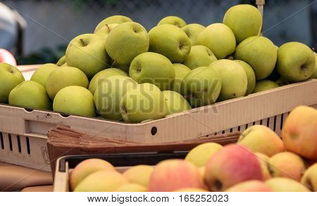 Bushel of green and red apples in a crate at a farmer's market with other fruits and vegetables.