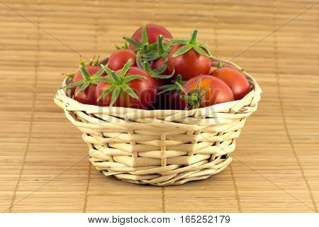 Still life with red tomatoes in wicker basket on straw mat closeup horizontal view