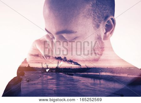 Double exposure image of a young man using a mobile phone and Gothenburg harbor in sunset.
