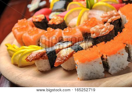 Nigiri sushi and sushi rolls with fish served on wooden table