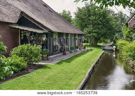 Facade of old residential house with a thatched roof in a small Dutch village of Giethoorn.