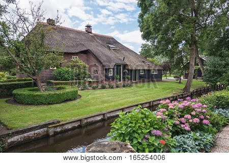 Old thatched farmhouse along the canal in the small Dutch town of Giethoorn.