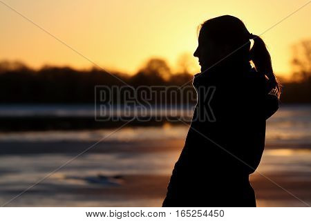 Silhouette of a woman at lake at sunset