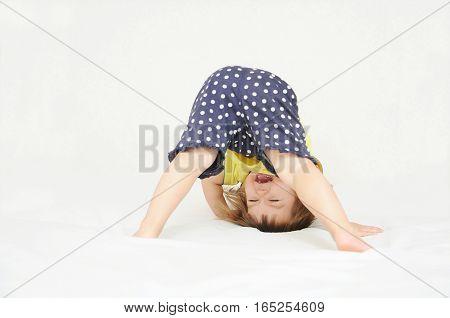 Happy Little Girl Standing On Head Upside Down